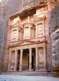 Al Khazneh ('The Treasury'; Arabic: الخزنة) is one of the most elaborate buildings in the ancient Jordanian city of Petra. As with most of the other buildings in this ancient town, including the Monastery (Arabic: Ad Deir), this structure was also carved out of a sandstone rock face. It has classical Greek-influenced architecture.<br/><br/>   Petra was first established as a city by the Nabataean Arabs in the 4th century BC, and owed its birth and prosperity to the fact that it was the only place with clear and abundant water between the Hijaz trading centres of Mecca and Medina, and Palestine.<br/><br/>   Hewn directly into the Nubian sandstone ridges of the south Jordanian desert, it seems probable that - given its excellent defensive position and good water supplies - Petra has been continually occupied from as early as Paleolithic times. It is thought to be mentioned in the Bible as Sela, a mountain fortress captured by Amaziah, King of Judah, in the 9th century BC, when the defenders were hurled to their deaths from the summit, and as many as 10,000 people died.<br/><br/>   The city's Latin name, Petra - literally, 'Rock' - probably replaced the biblical name Sela at the time of the Roman conquest some 1,900 years ago. Today, in Arabic, the ancient site is still called Batraa, though the valley in which it is situated is known as Wadi Musa - 'The Valley of Moses' - being one of the places where, according to semitic tradition, the Prophet Moses struck a rock and water gushed forth. Truly Petra is steeped in history.